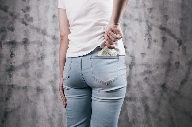 Mano de mujer poniendo dinero en el bolsillo de los pantalones vaqueros