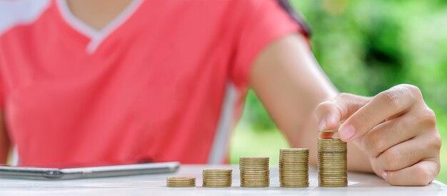 Mano de mujer poniendo monedas, monedas de oro pila en mesa de madera