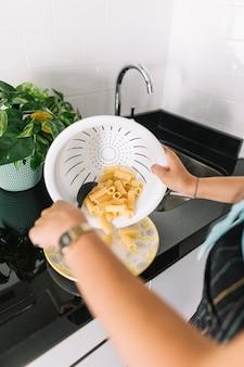 Mano de mujer poniendo pasta de rigatoni de colador blanco en un plato