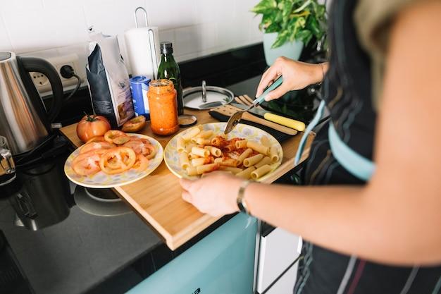 Mano de mujer preparando deliciosas pastas en el mostrador de la cocina