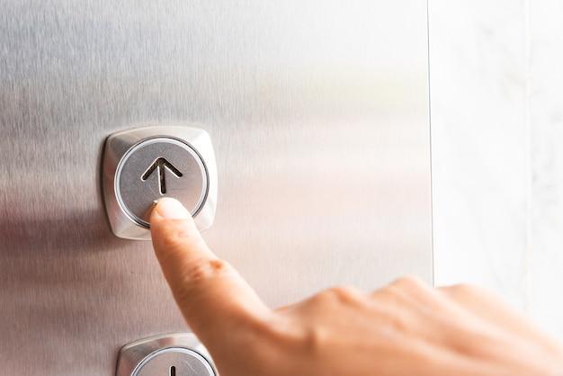 La mano de la mujer presiona un botón ascendente del elevador dentro del edificio.
