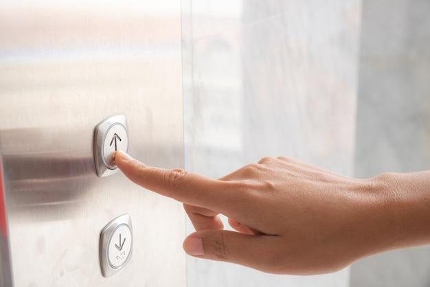 Mano de mujer presione un botón arriba del elevador dentro del edificio