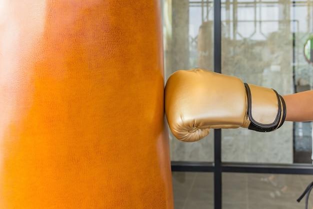 Mano de mujer de primer plano de boxeador en el momento del impacto en el saco de arena en el gimnasio