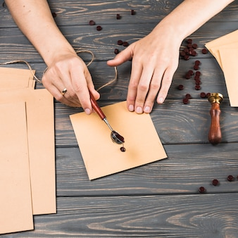 La mano de la mujer del primer que vierte la cera del derretimiento encima envuelve en el fondo de madera de la textura