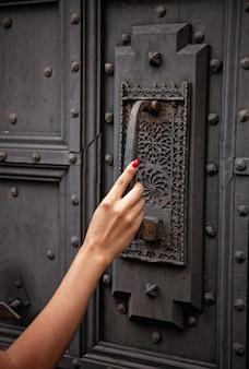 Mano de mujer en la puerta antigua