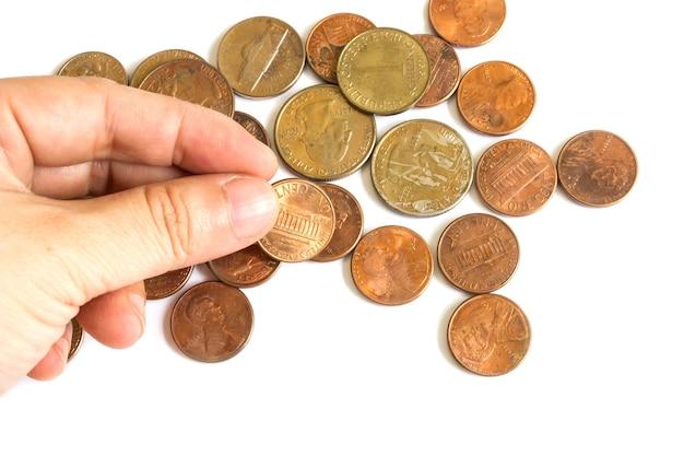 La mano de la mujer que escoge moneda de los eeuu en el fondo blanco.