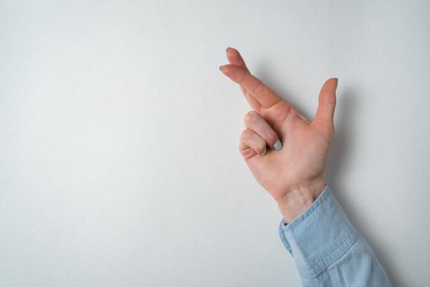 La mano de la mujer que hace los dedos cruzados en la pared blanca. gesto de suerte.