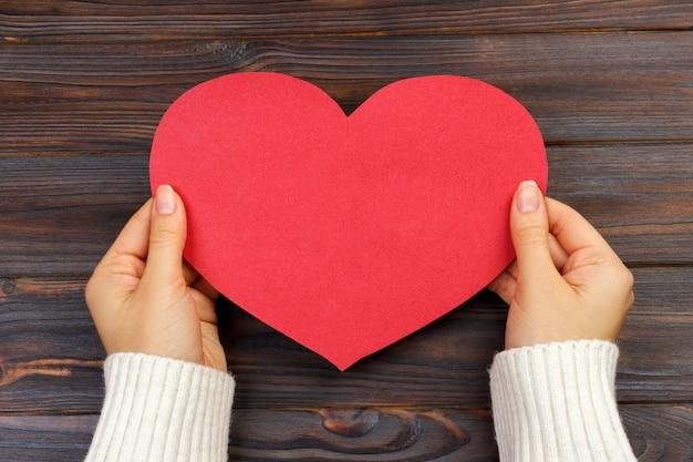 Mano de la mujer que lleva a cabo la forma roja de papel del corazón copia espacio