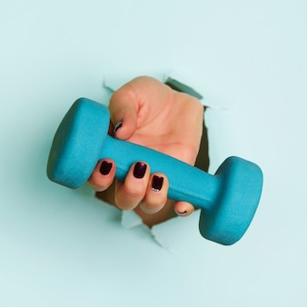 Mano de la mujer que lleva a cabo pesa de gimnasia azul en fondo azul