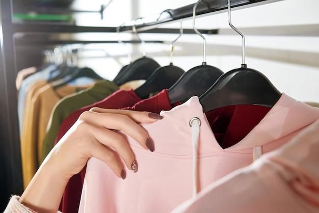 La mano de la mujer que miente en perchas de la tienda con ropa.