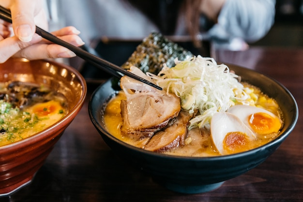 Mano de la mujer que pellizca los tallarines en la sopa del hueso del cerdo de ramen (ramen de tonkotsu) con el cerdo de chashu