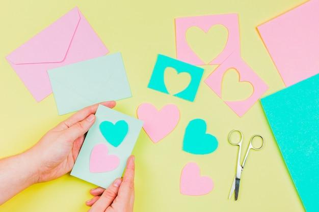 La mano de la mujer que prepara la tarjeta de felicitación de la forma del corazón en fondo amarillo