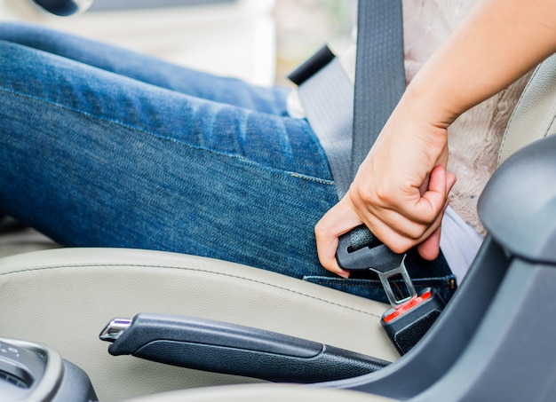 Mano de la mujer que se sienta dentro del cinturón de seguridad de la cerradura del coche. cinturón de seguridad de seguridad primero.