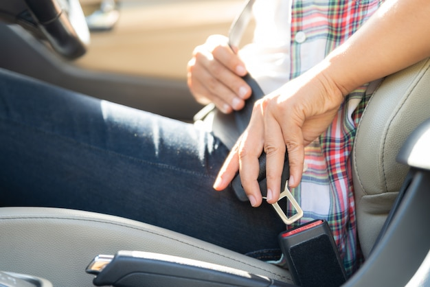 Mano de la mujer que se sienta dentro del cinturón de seguridad de la cerradura del coche. seguridad del cinturón de seguridad primero.