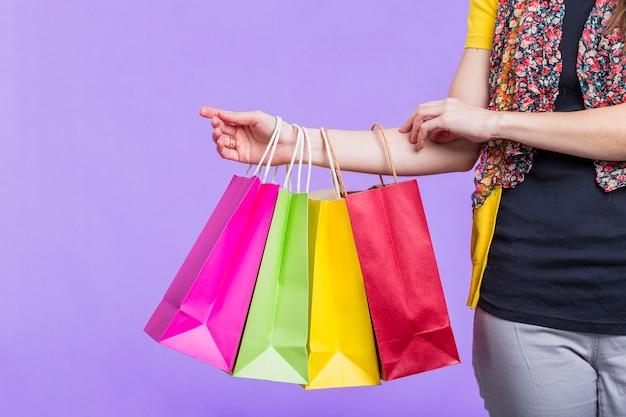 Mano de la mujer que sostiene el bolso de compras colorido en fondo púrpura