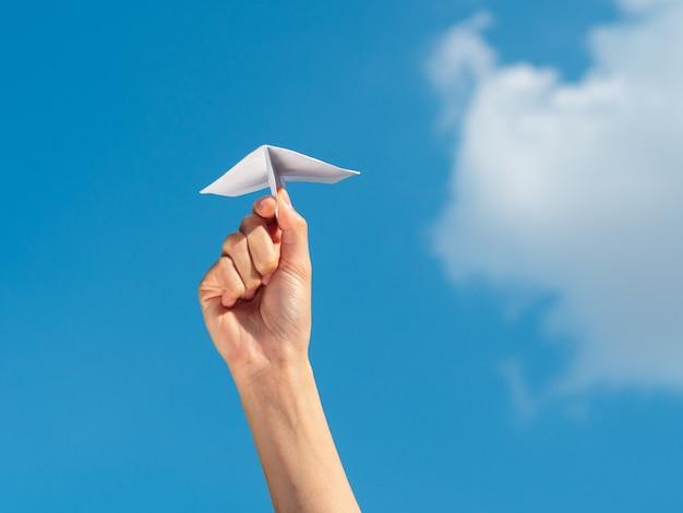 Mano de la mujer que sostiene el cohete de papel con el fondo del cielo azul. concepto de libertad