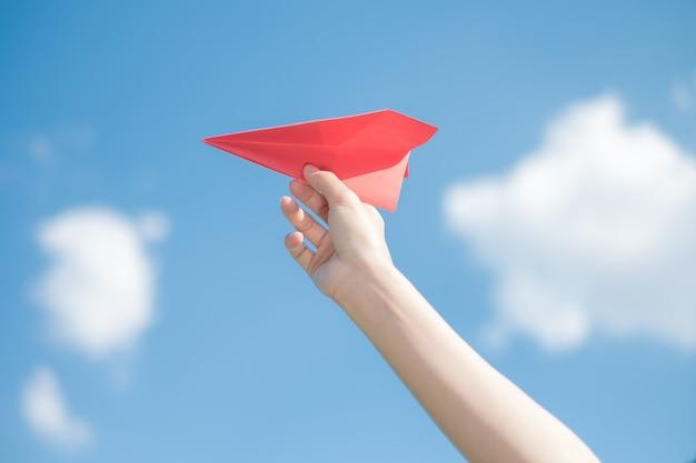 Mano de la mujer que sostiene un cohete de papel rojo con un fondo azul brillante.