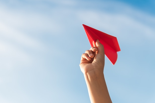 Mano de la mujer que sostiene el cohete de papel rojo con el fondo del cielo azul.