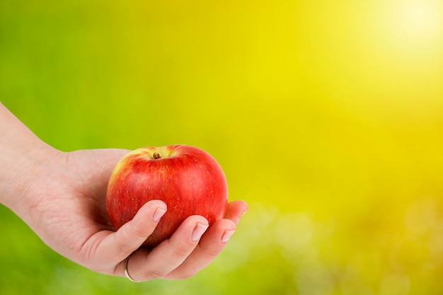La mano de la mujer que sostiene la manzana roja contra fondo natural verde.
