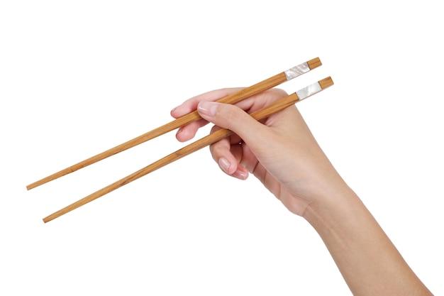 Mano de la mujer que sostiene los palillos aislados en blanco