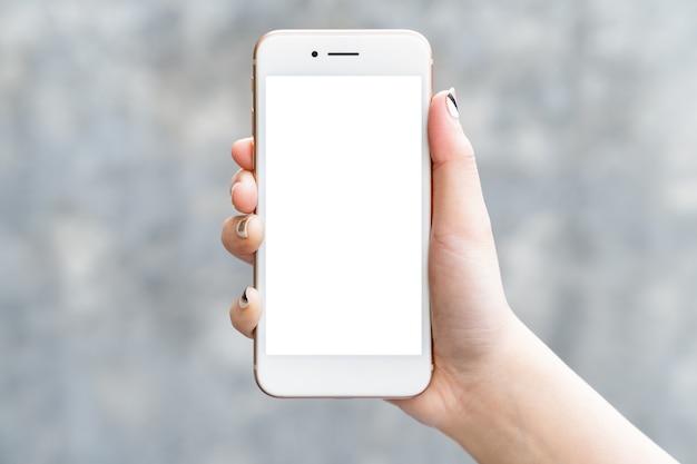 Mano de mujer que sostiene la pantalla blanca aislada del smartphone de la maqueta para el diseño o la exhibición de la aplicación