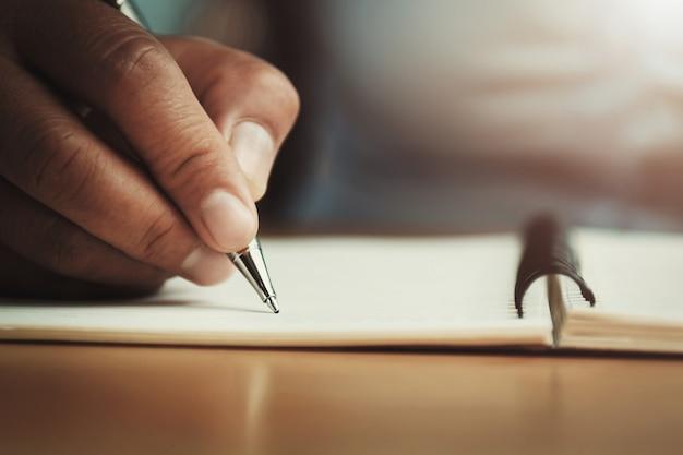 Mano de la mujer que sostiene la pluma con la escritura en el cuaderno en oficina