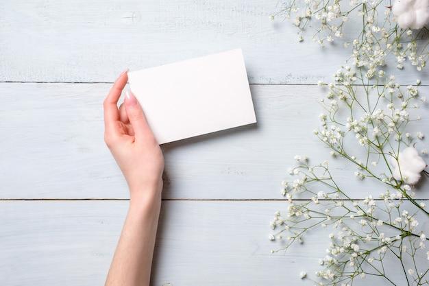 Mano para mujer que sostiene la tarjeta de papel en blanco en fondo de madera azul claro.