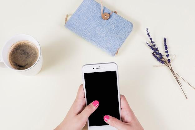 La mano de la mujer que sostiene el teléfono celular con la taza de café; diario y lavanda en el fondo