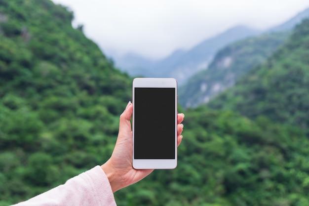Mano de la mujer que sostiene el teléfono elegante en el parque natural al aire libre, el negocio de la tecnología espacial de la copia y el concepto de vacaciones de la naturaleza del viaje