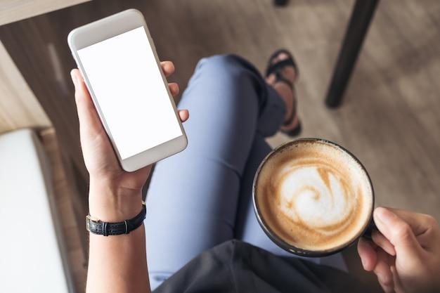 La mano de una mujer que sostiene el teléfono móvil blanco con la pantalla de escritorio en blanco mientras que bebe el café