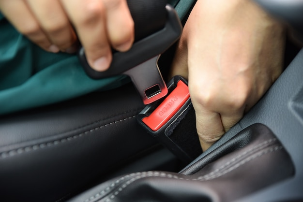 Mano de la mujer que sujeta un cinturón de seguridad en el coche. concepto de seguridad del coche