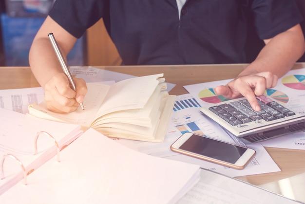 La mano de la mujer que usa la calculadora y la escritura hacen la nota con calcula