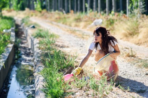 Mano de mujer recogiendo basura de la hierba en el campo