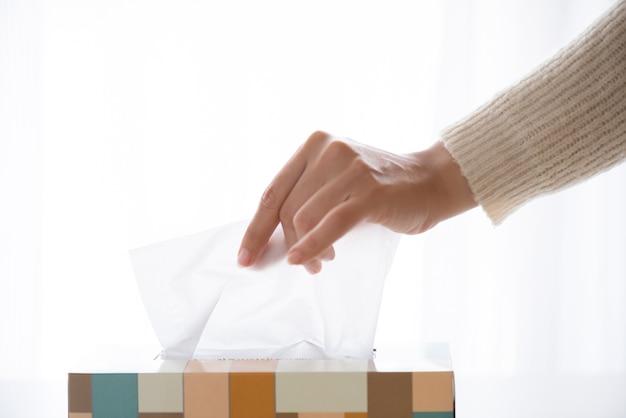 Mano de mujer recogiendo papel de seda blanco de la caja de pañuelos. concepto de salud.