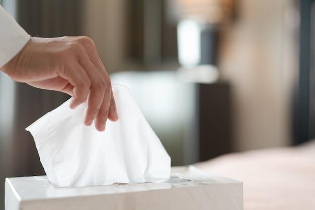 Mano de mujer recogiendo servilleta / papel de seda de la caja de pañuelos