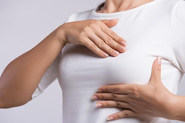 Mano de mujer revisando bultos en su seno para detectar signos de cáncer de seno