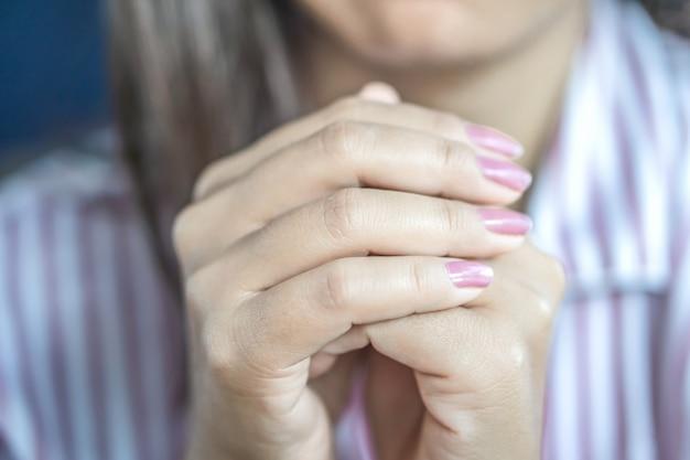 Mano de mujer rezando pacíficamente antes de dormir
