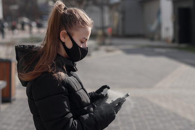 La mano de la mujer está rociando alcohol, aerosol desinfectante en el teléfono móvil, previene la infección del virus covid-19, la contaminación de gérmenes o bacterias, limpia o limpia el teléfono para eliminar, brote de coronavirus