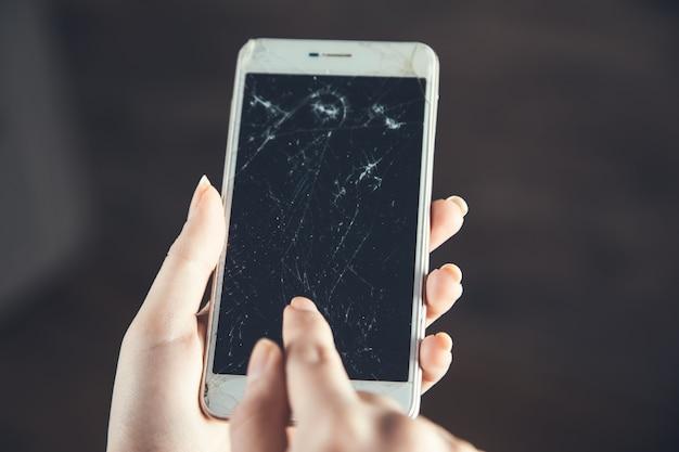 Mano de mujer rota teléfono inteligente sobre fondo marrón