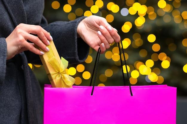 Mano de mujer saca una caja de regalo de la bolsa de compras en el fondo de bokeh y luces borrosas. espacio vacio