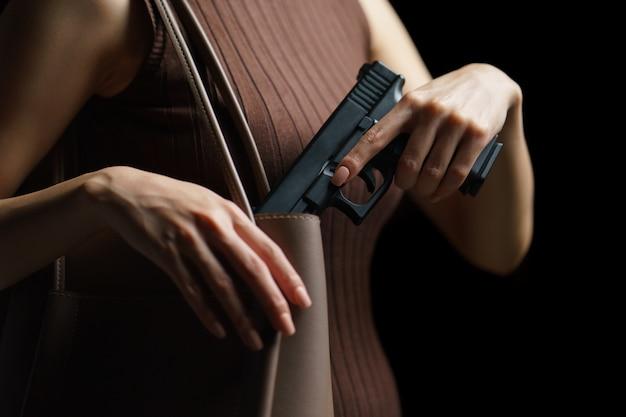 Mano de mujer sacando una pistola del bolso.