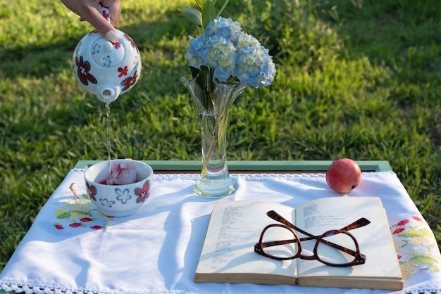 Mano de mujer sirviendo té en la mesa de lectura al atardecer campo