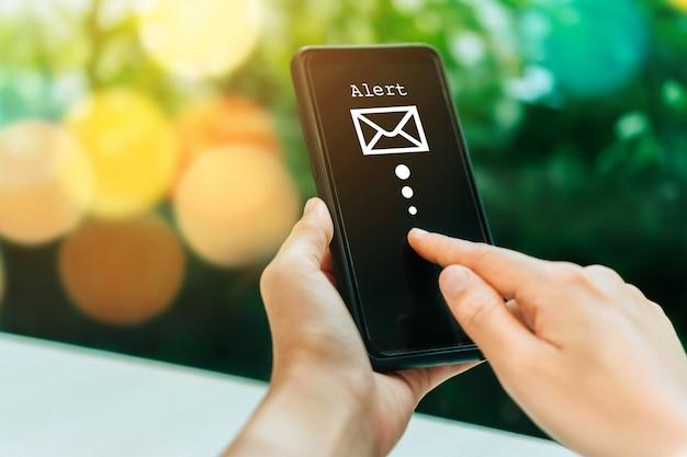 Mano de mujer con smartphone para enviar y recibir correo electrónico.