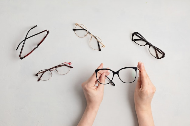 Mano de mujer sosteniendo anteojos. tienda de óptica, selección de gafas, examen ocular, examen de la vista en el óptico, concepto de accesorios de moda. vista superior, endecha plana