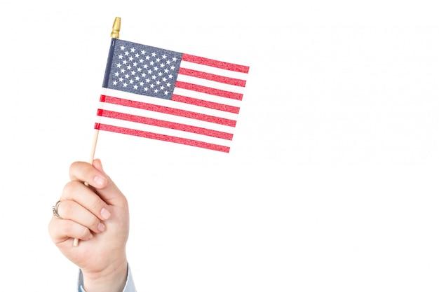 Mano de mujer sosteniendo la bandera americana de los estados unidos con estrellas y rayas aisladas en blanco