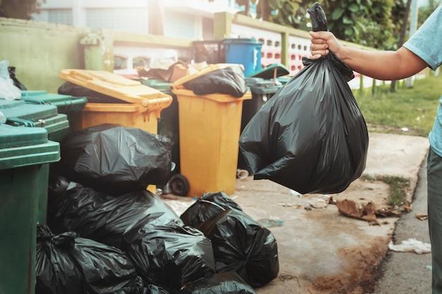 Mano de mujer sosteniendo basura en bolsa negra para limpiar en basura