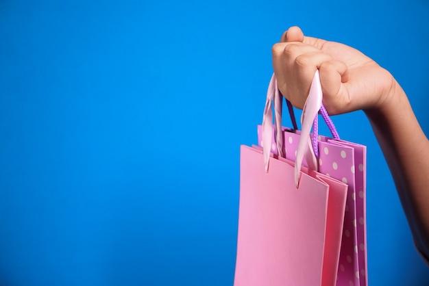 Mano de mujer sosteniendo la bolsa de compras sobre fondo azul,
