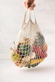 Mano de mujer sosteniendo una bolsa de frutas y verduras mixtas