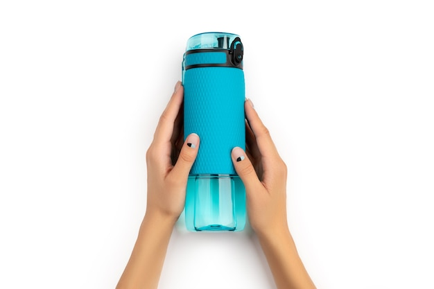 Mano de mujer sosteniendo una botella de agua azul aislado sobre fondo blanco.
