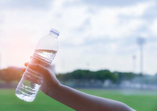 Mano de mujer sosteniendo una botella de agua potable en cielo azul y campo verde